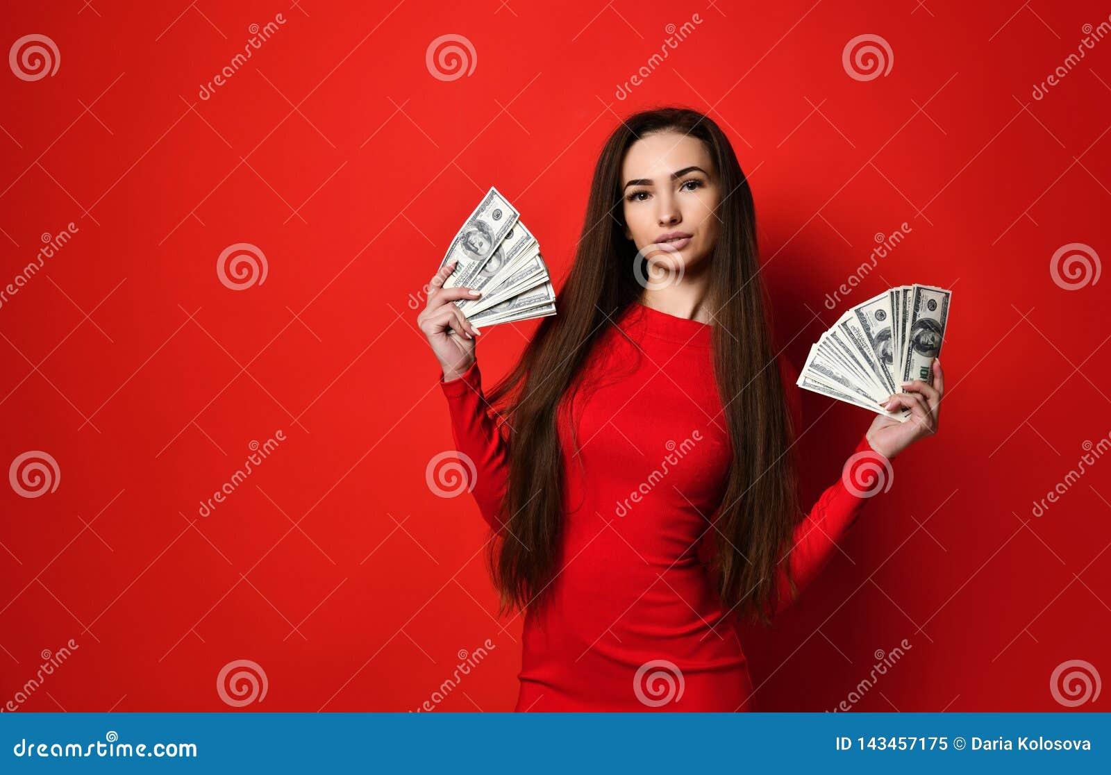 Giovane donna graziosa in vestito rosso che si nasconde dietro il mazzo di banconote dei soldi