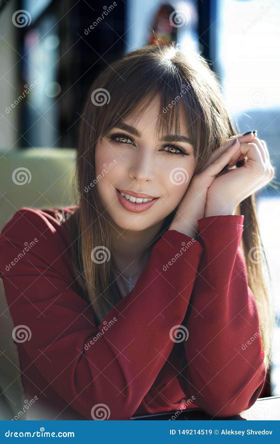 Giovane donna incantante con il sorriso amichevole, caff? sorridente del ritratto dei capelli castana lunghi