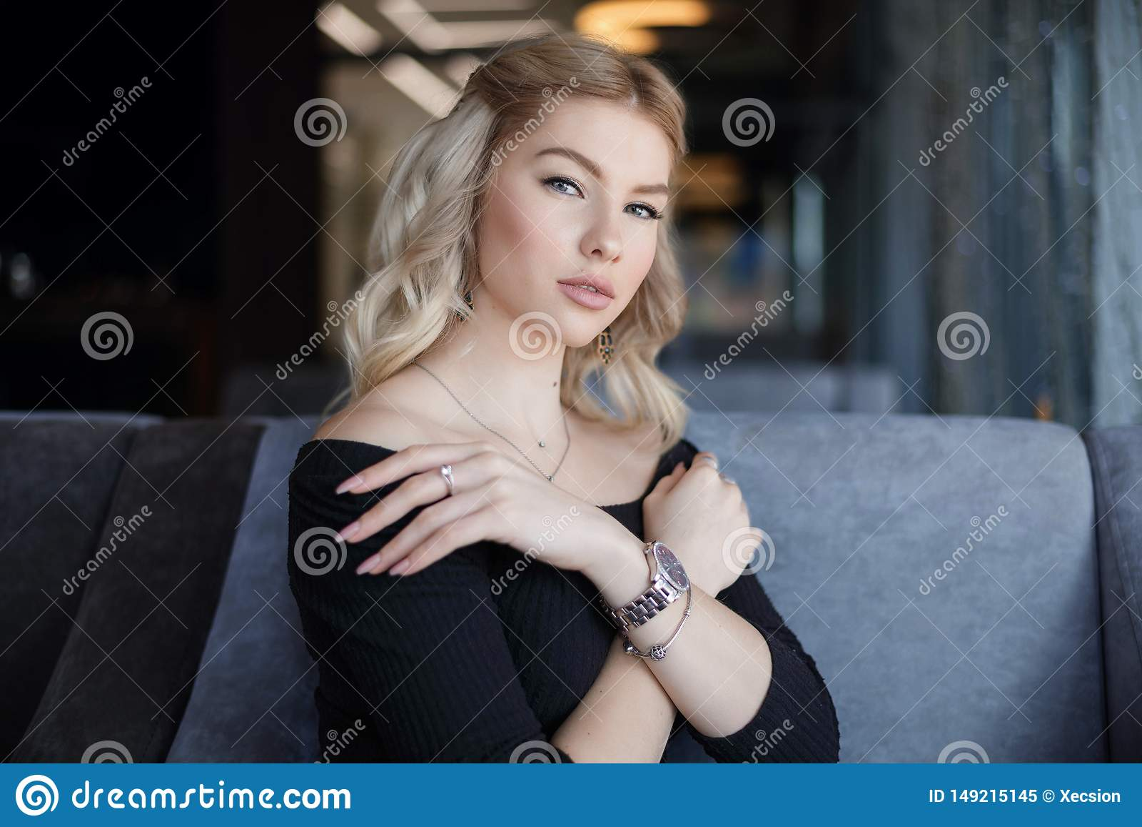 Giovane donna incantante del ritratto con il sorriso amichevole, sorridere lungo dei capelli biondi