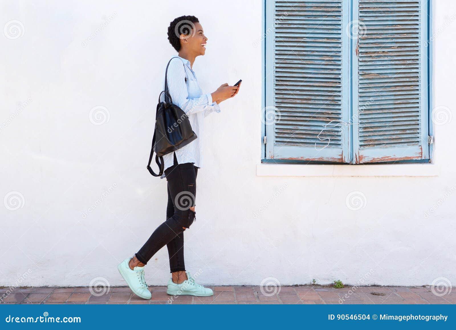 Giovane donna integrale che cammina con il cellulare e la borsa
