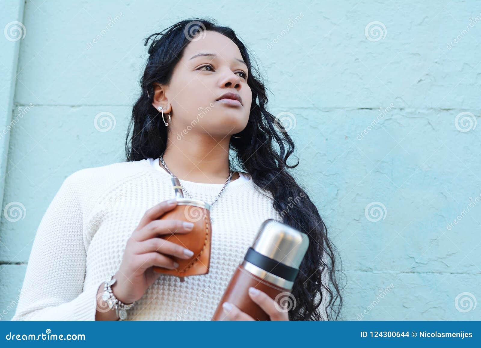 Giovane donna latina che beve il tè tradizionale dell erba mate