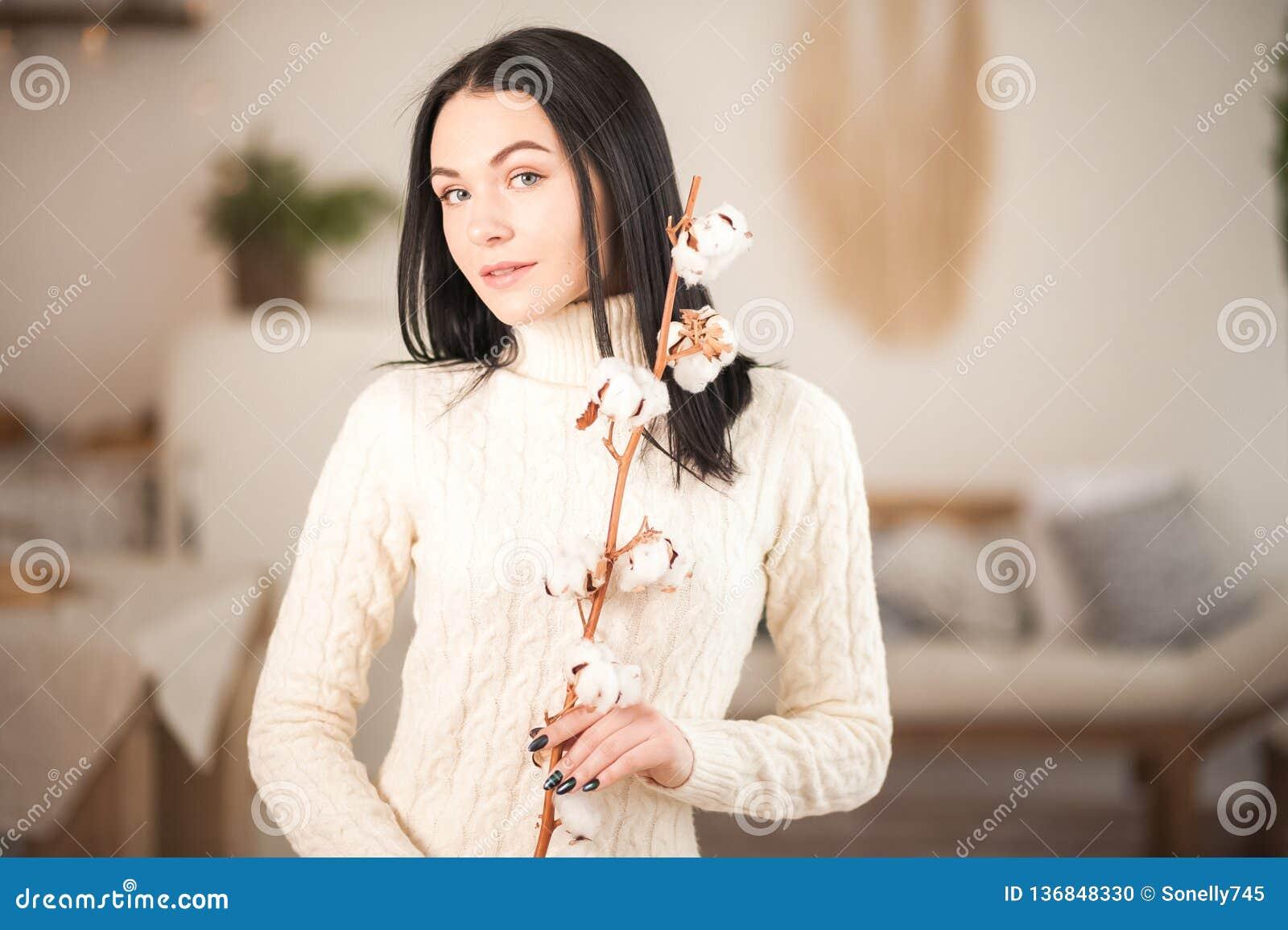 Giovane donna in maglione bianco tricottato del vestito con un ramo del primo piano del cotone Ragazza nell interno romantico d a