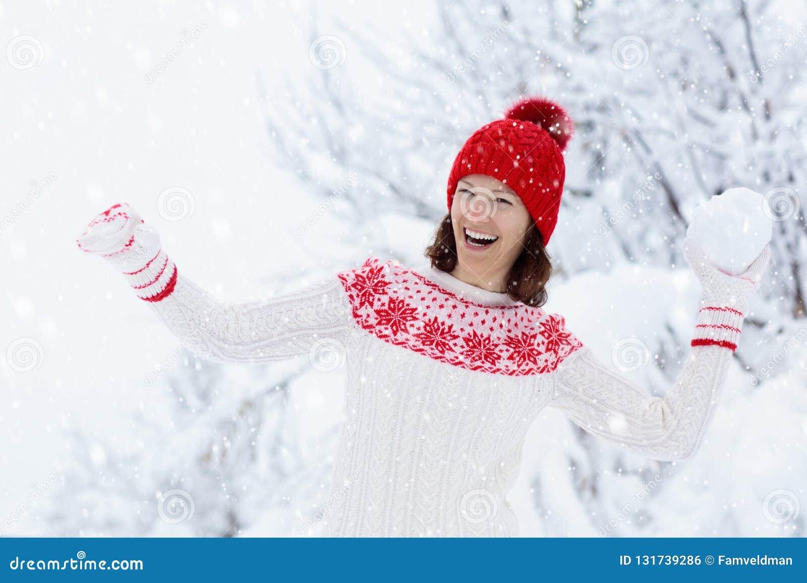Giovane donna in maglione tricottato che gioca lotta della palla della neve nell inverno Gioco di palle in famiglia della neve de