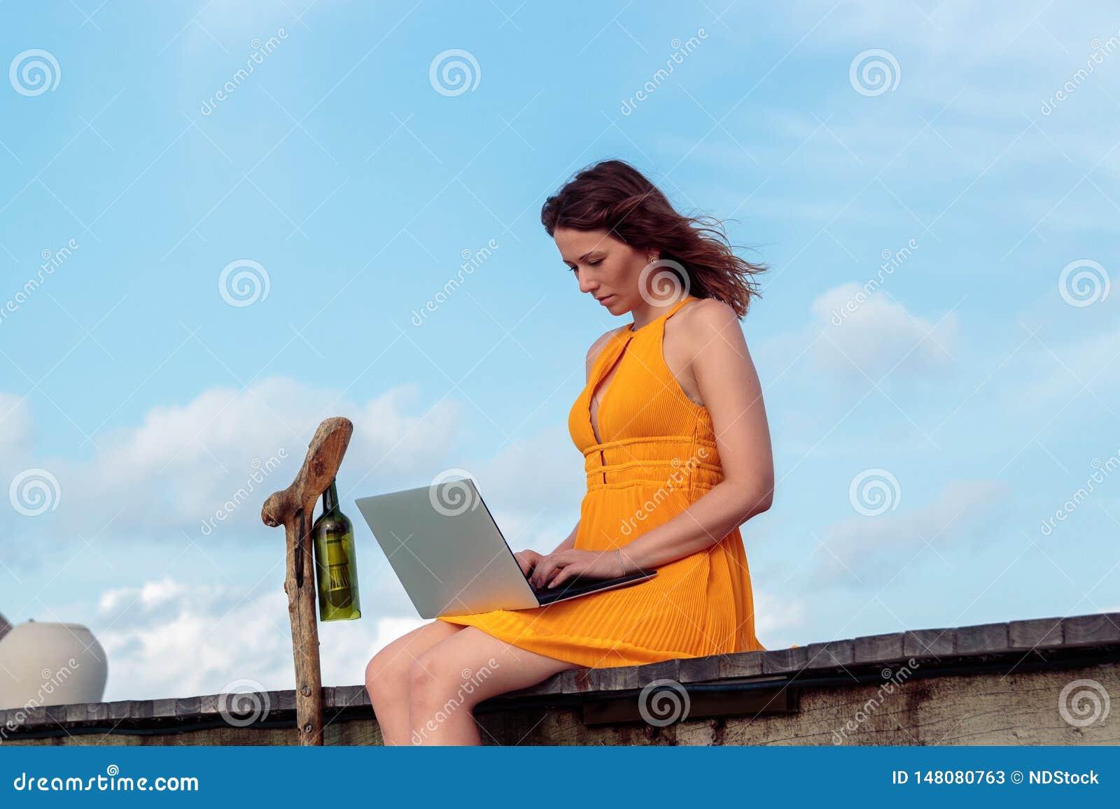 Giovane donna messa su un pilastro e sul lavoro con il suo computer portatile Cielo blu come fondo