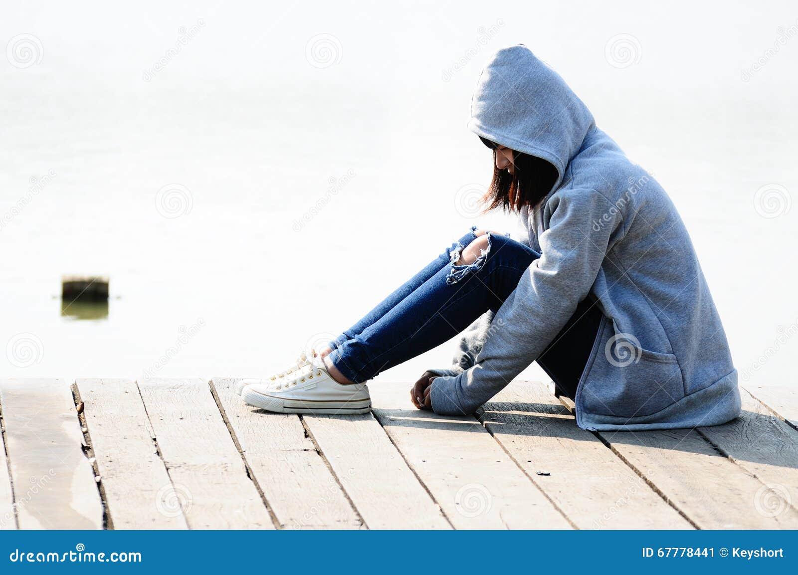 Giovane donna nella disperazione che si siede vicino al fiume