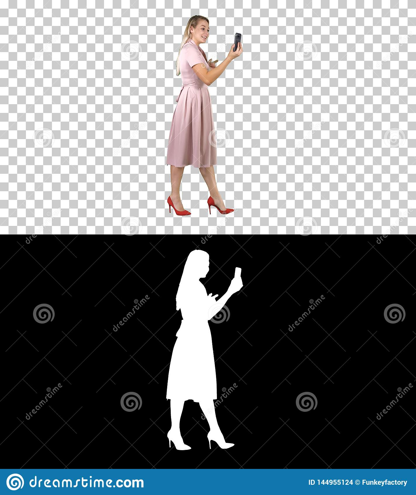 Giovane donna nella tenuta rosa facendo uso del blog video di registrazione dello Smart Phone mentre camminando, Alpha Channel