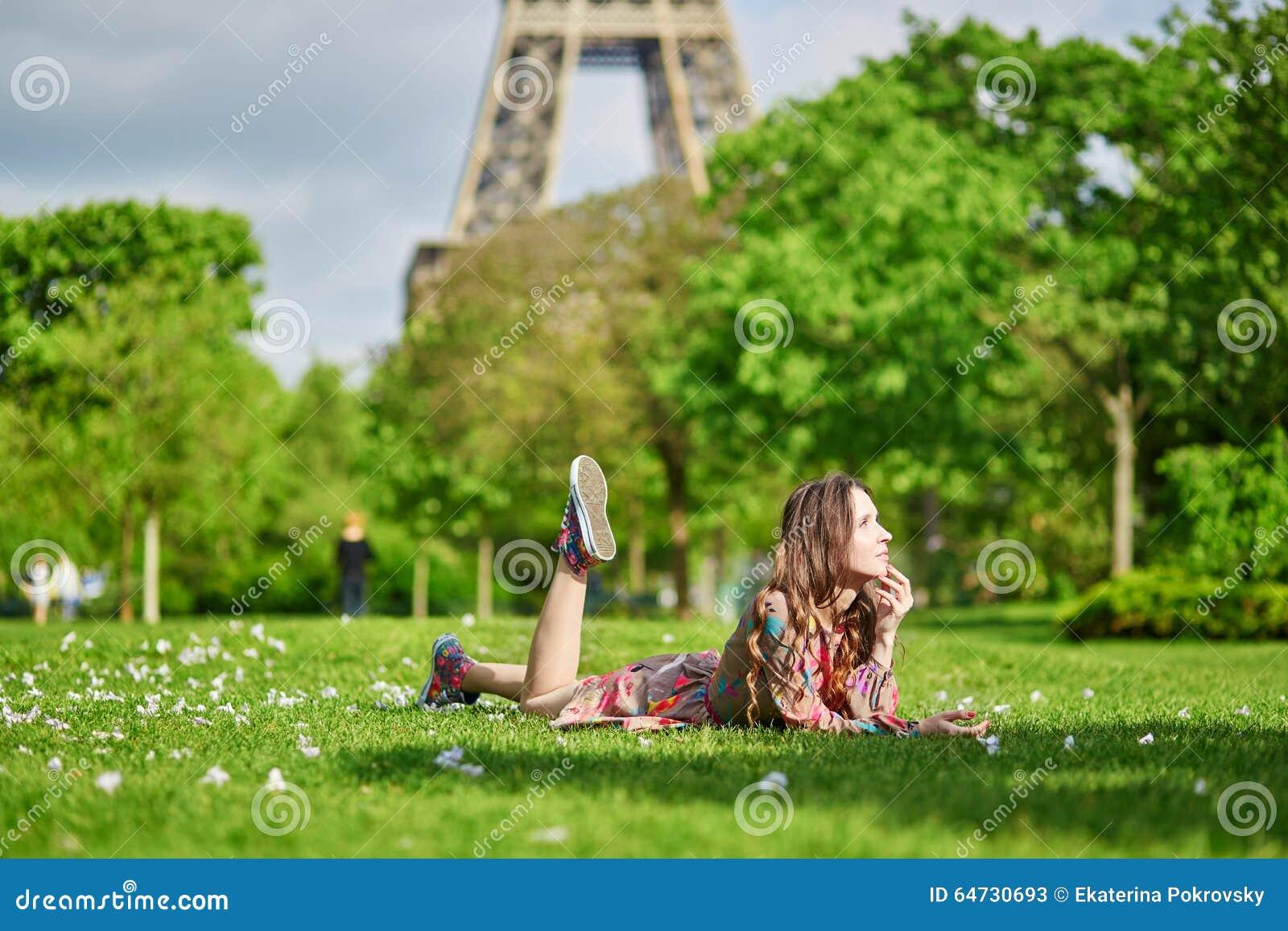 Giovane donna a Parigi che si trova sull erba vicino alla torre Eiffel un giorno piacevole di estate o della primavera
