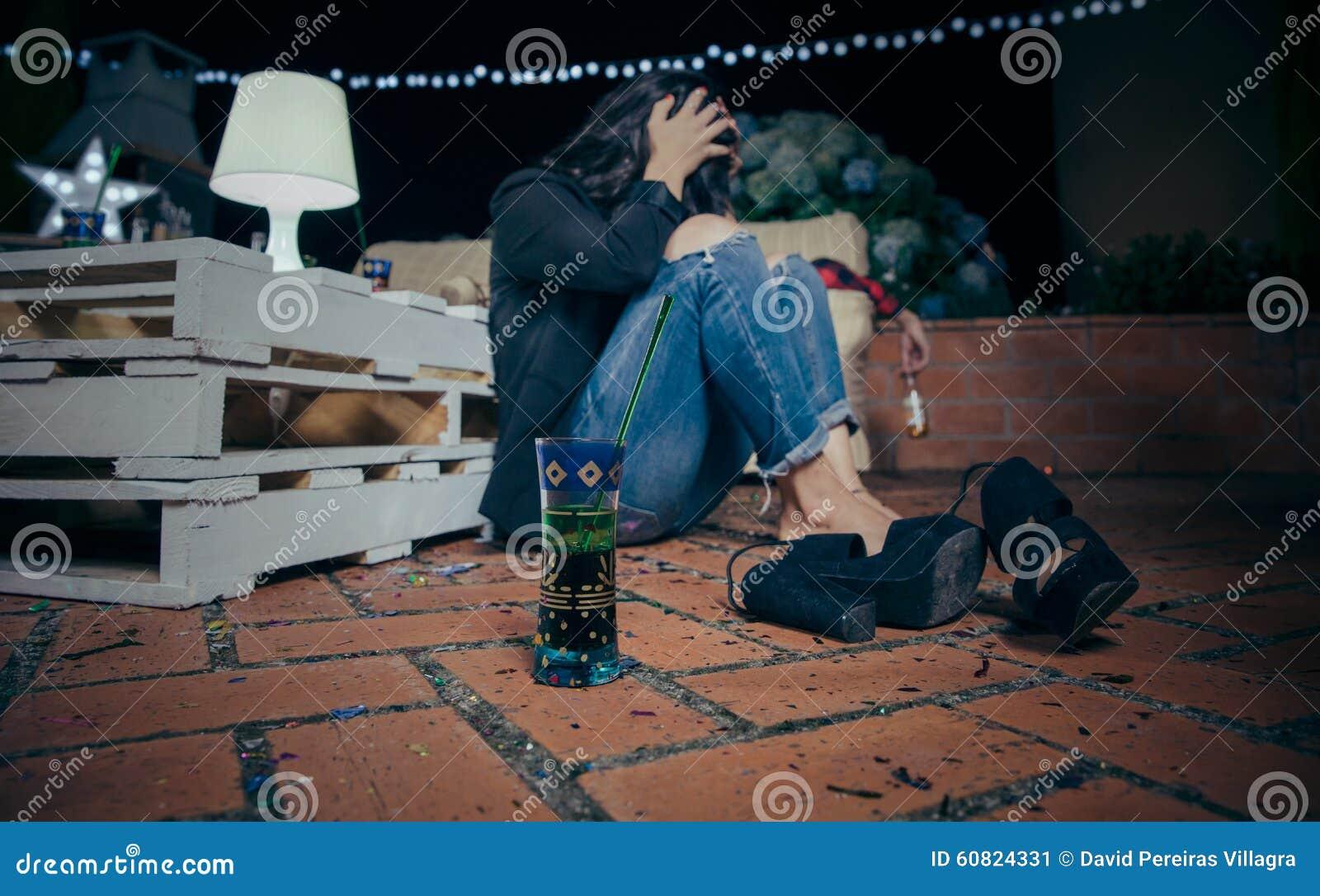 Giovane donna potabile che si siede nel pavimento dopo il partito