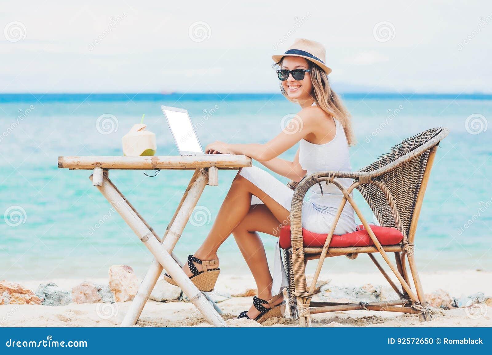 Giovane donna sexy che per mezzo del computer portatile sulla spiaggia Freelance il lavoro