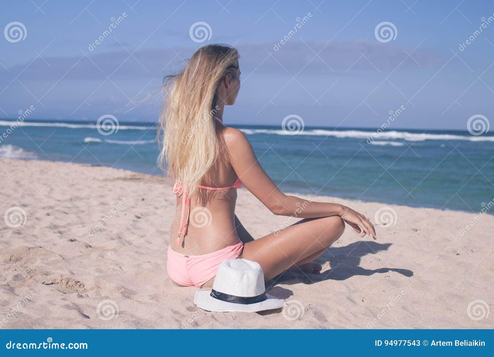 Giovane donna sexy sola che si siede sulla spiaggia - Donne che vanno in bagno a cagare ...