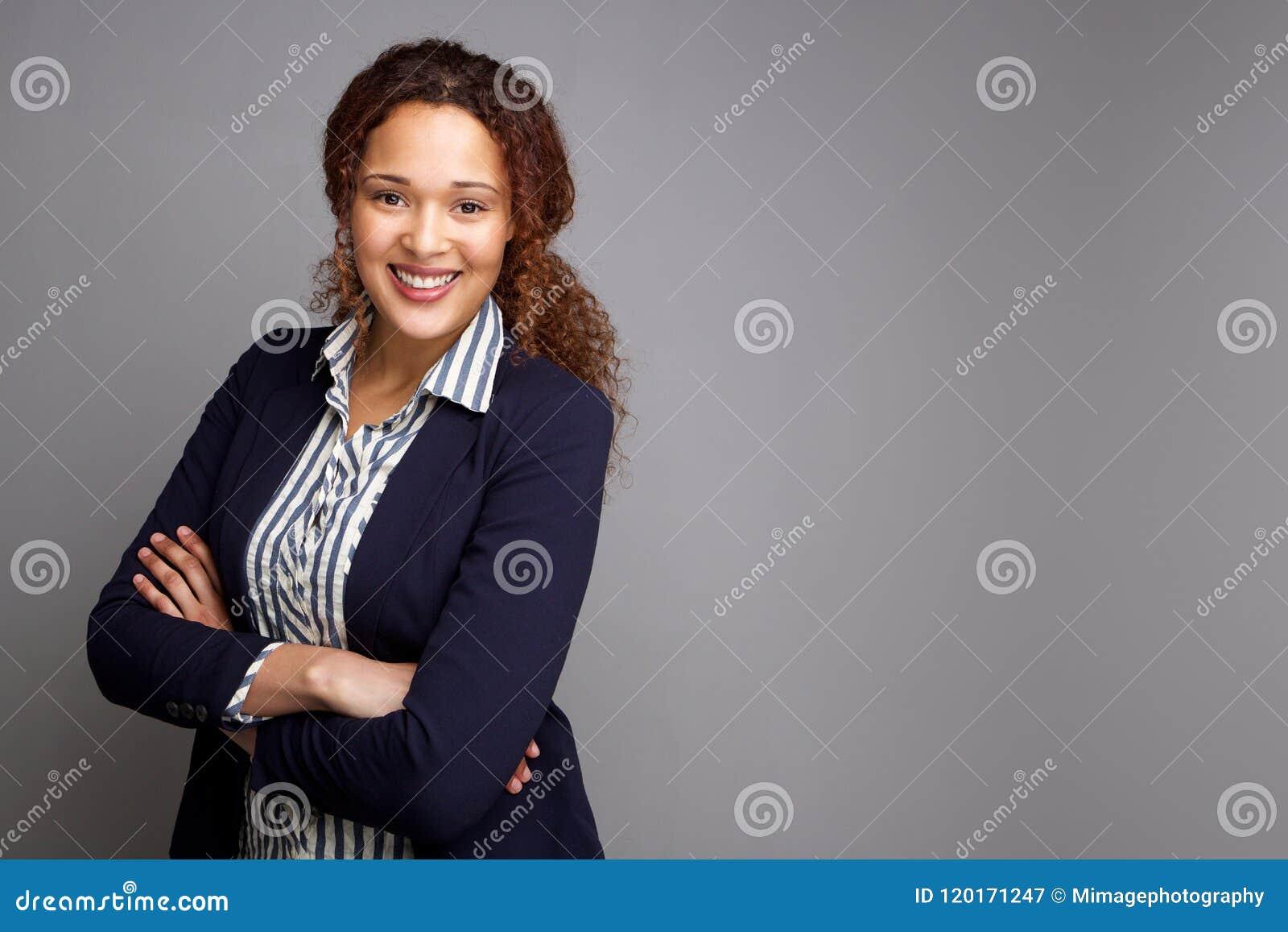 Giovane donna sicura di affari che sorride umiliando fondo grigio