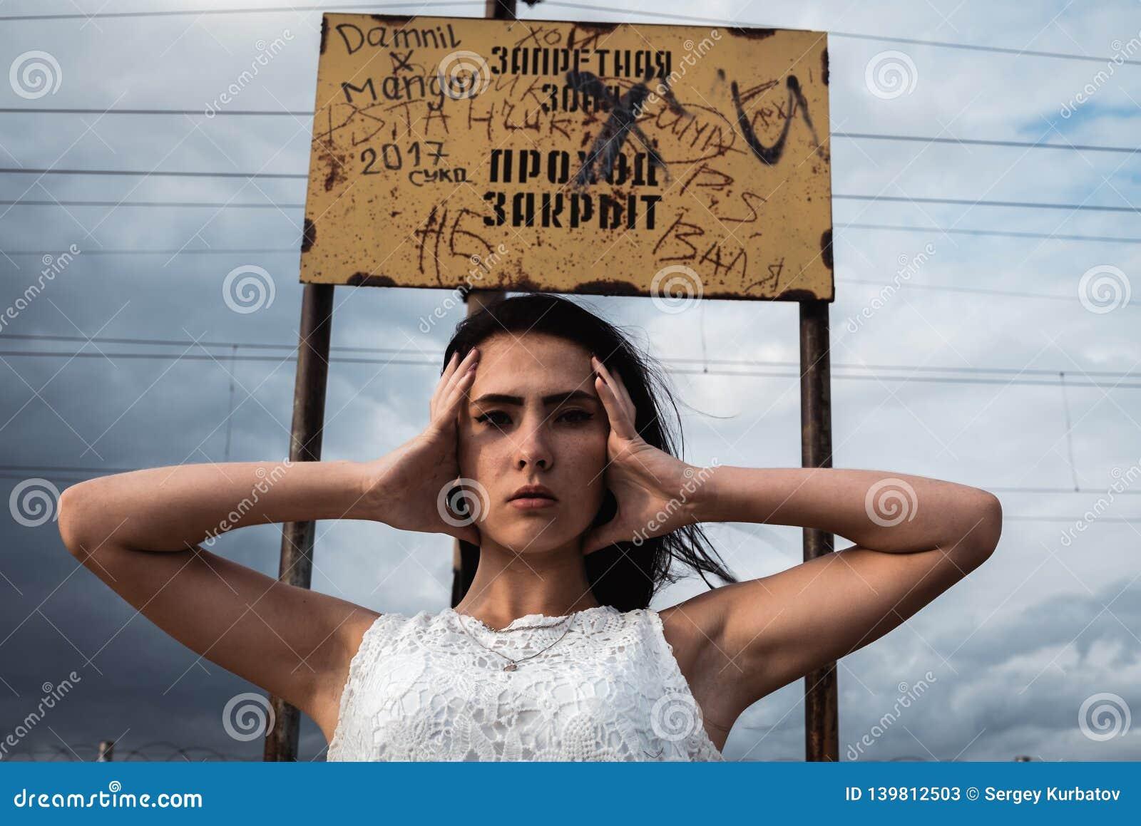 Giovane donna sollecitata premurosa tiene la sua testa in sue mani