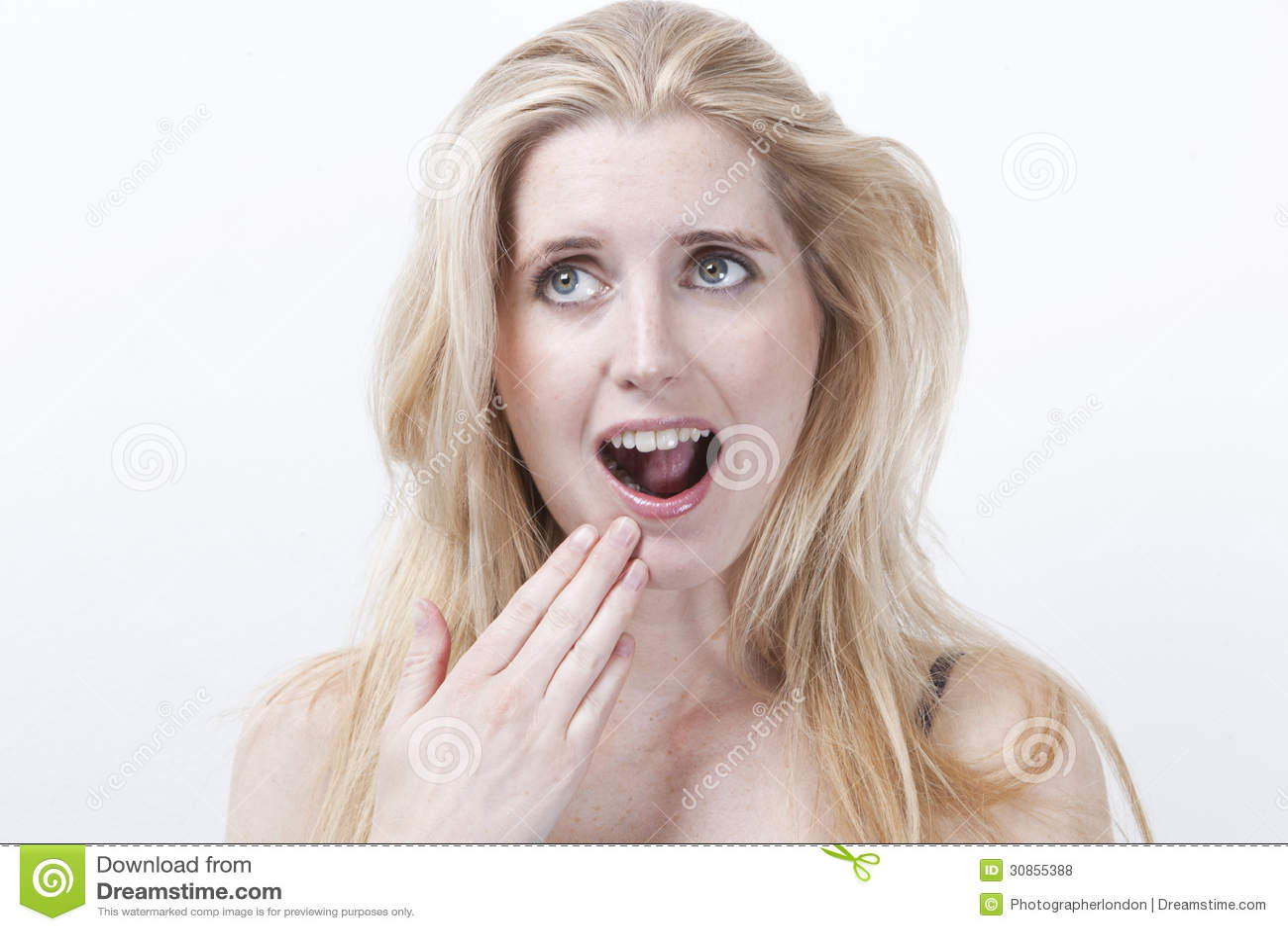 Giovane donna sorpresa con la bocca aperta contro fondo bianco