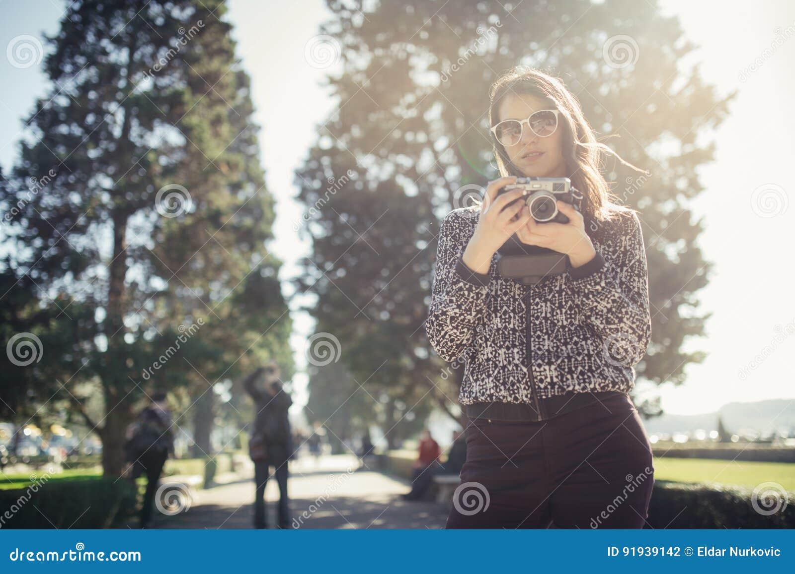 Giovane donna sorridente che parla sul suo smartphone sulla via Comunicando con gli amici, liberi le chiamate ed i messaggi per i