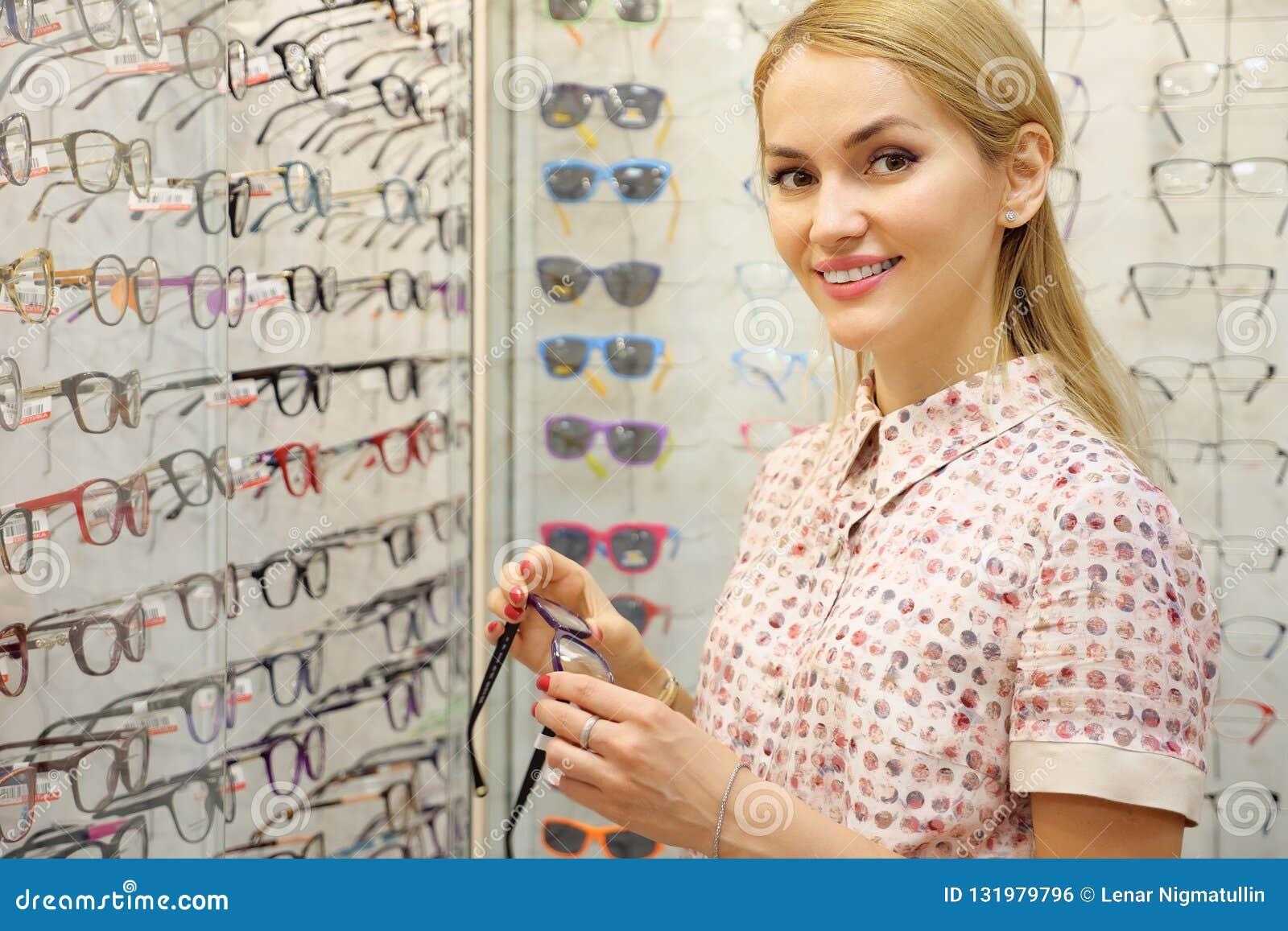 Giovane donna sorridente che prova i nuovi vetri al deposito dell ottico