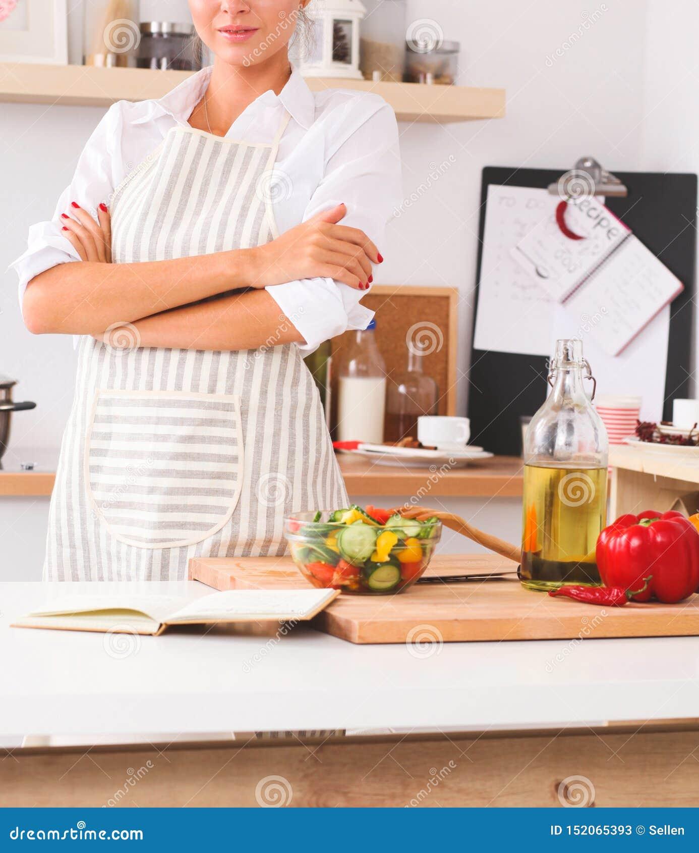Giovane donna sorridente nella cucina, isolata sul fondo di natale