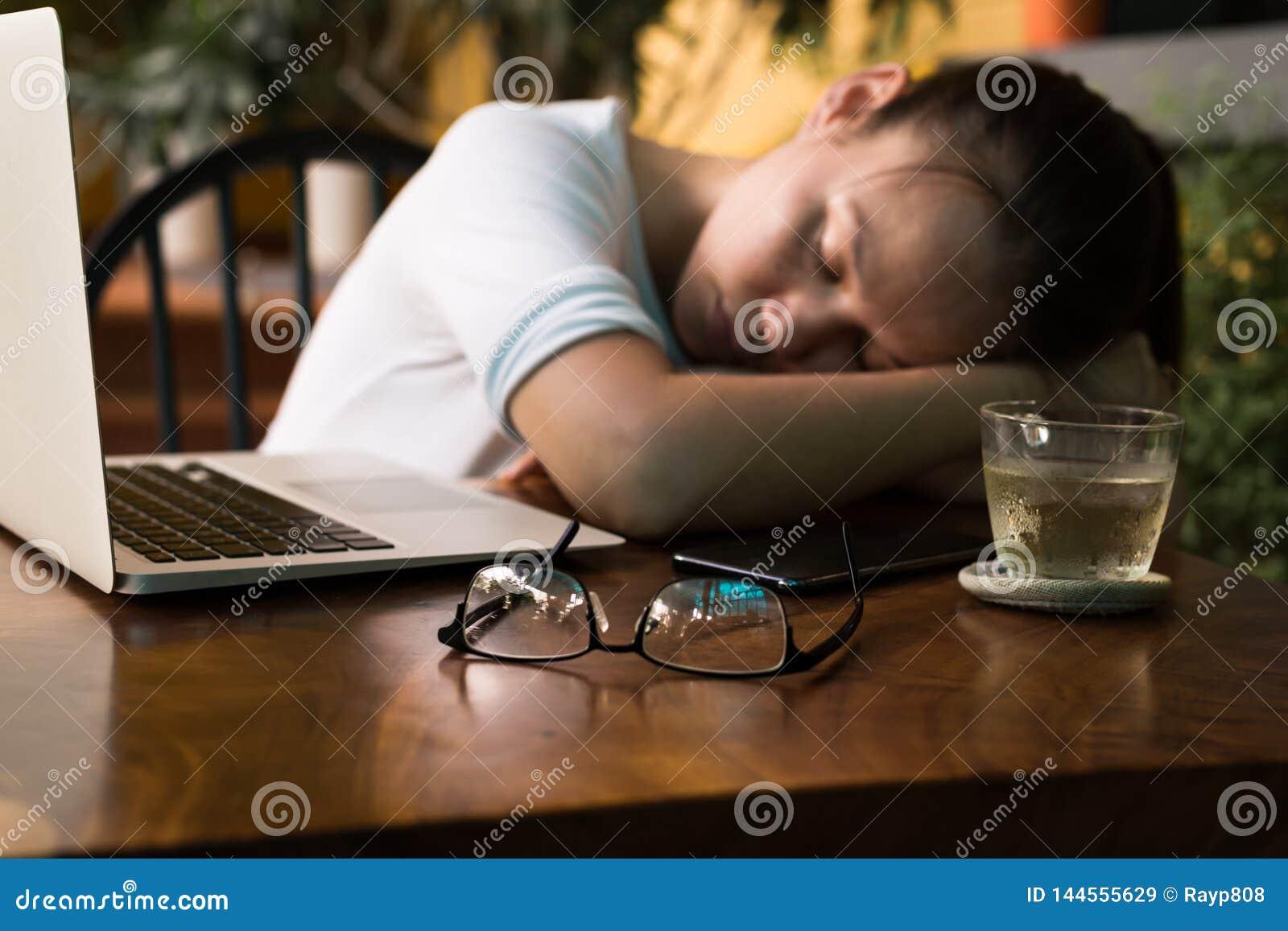 Giovane donna stanca che dorme sul suo scrittorio del computer