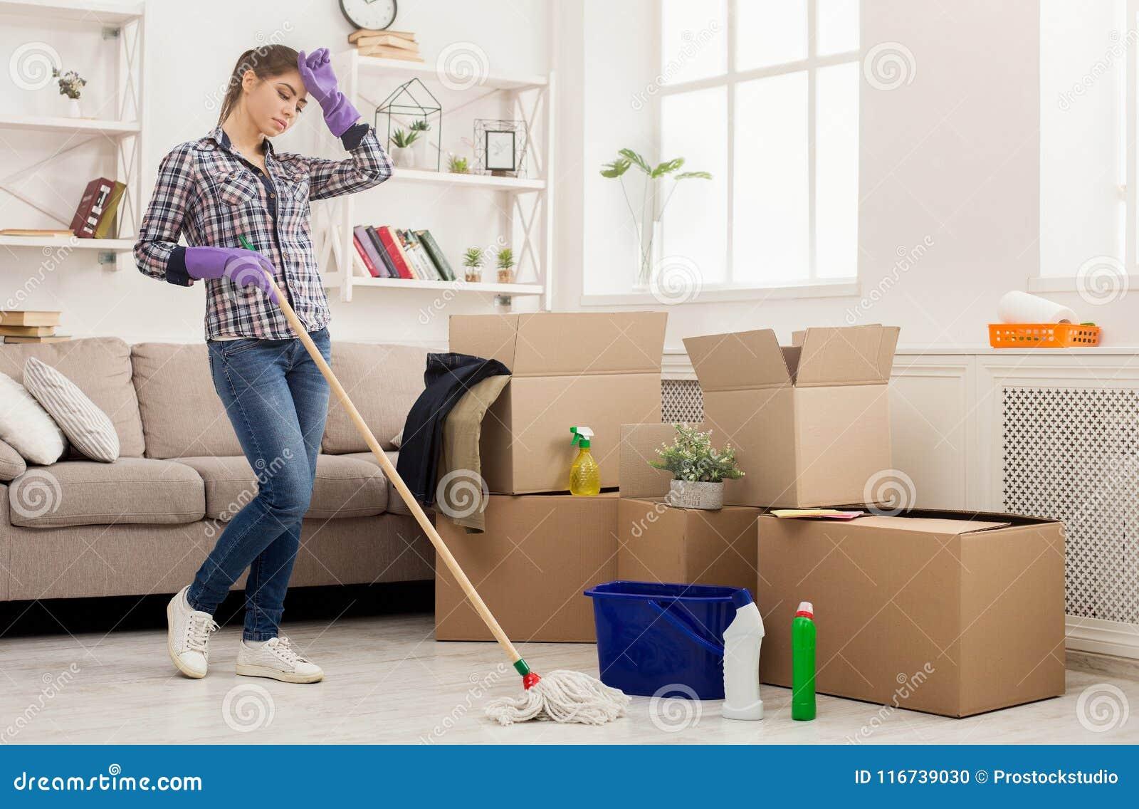 Giovane donna stanca che pulisce nuova casa con la zazzera