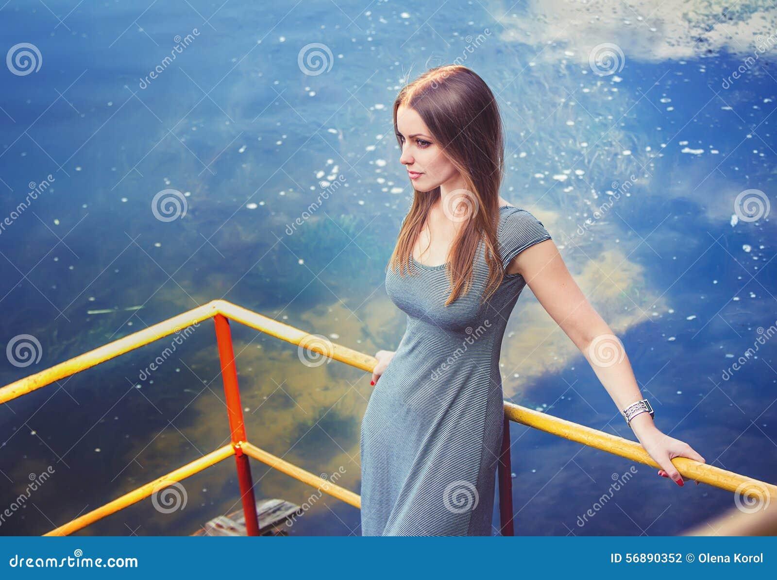 Giovane donna sul pilastro del fiume