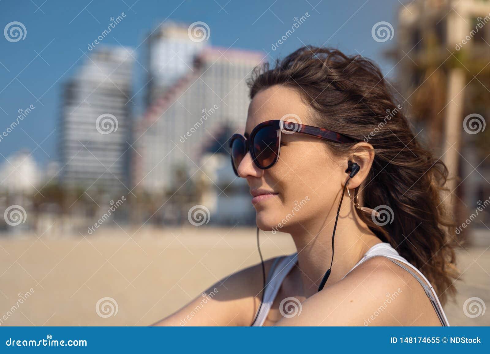 Giovane donna sulla musica d ascolto della spiaggia con le cuffie orizzonte della citt? come fondo