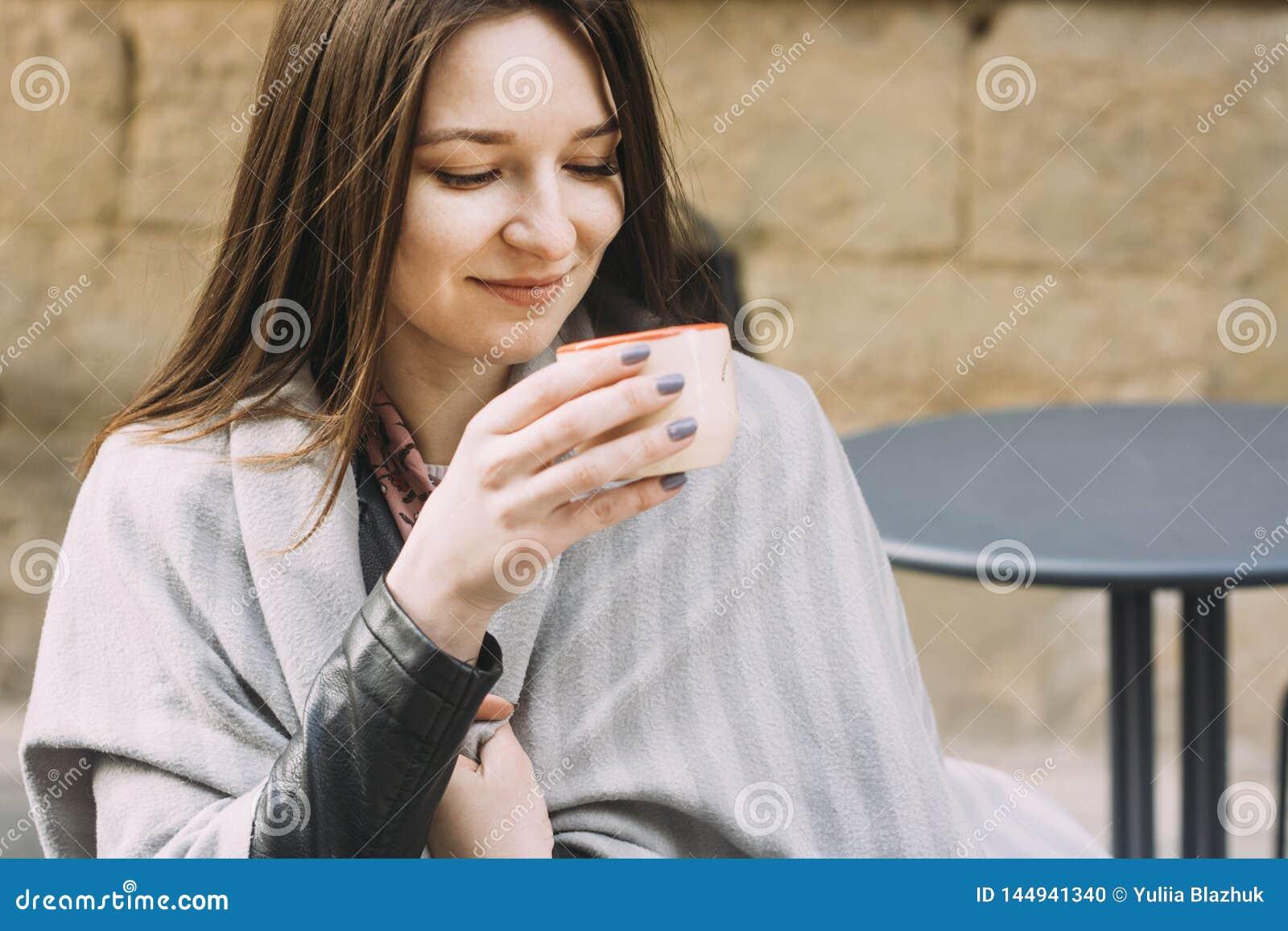 Giovane donna in un caffè bevente del caffè della via