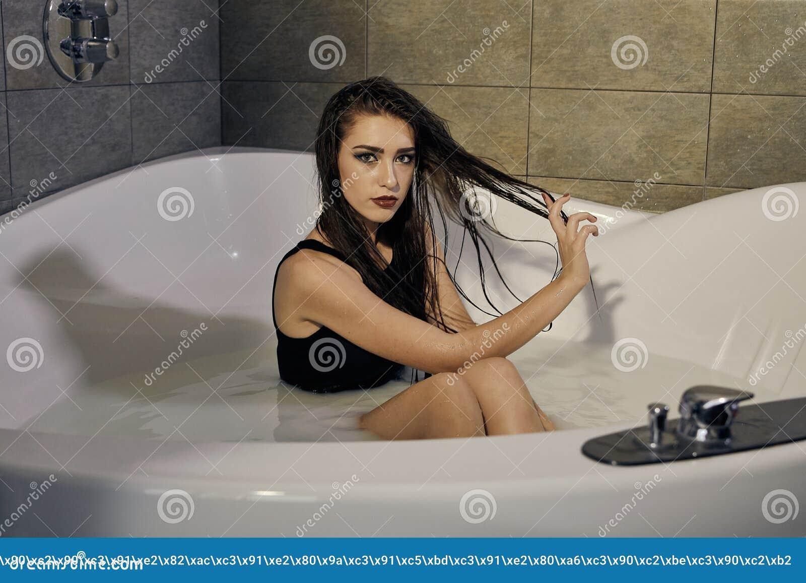 Giovane donna in un costume da bagno nero che posa nel bagno di latte