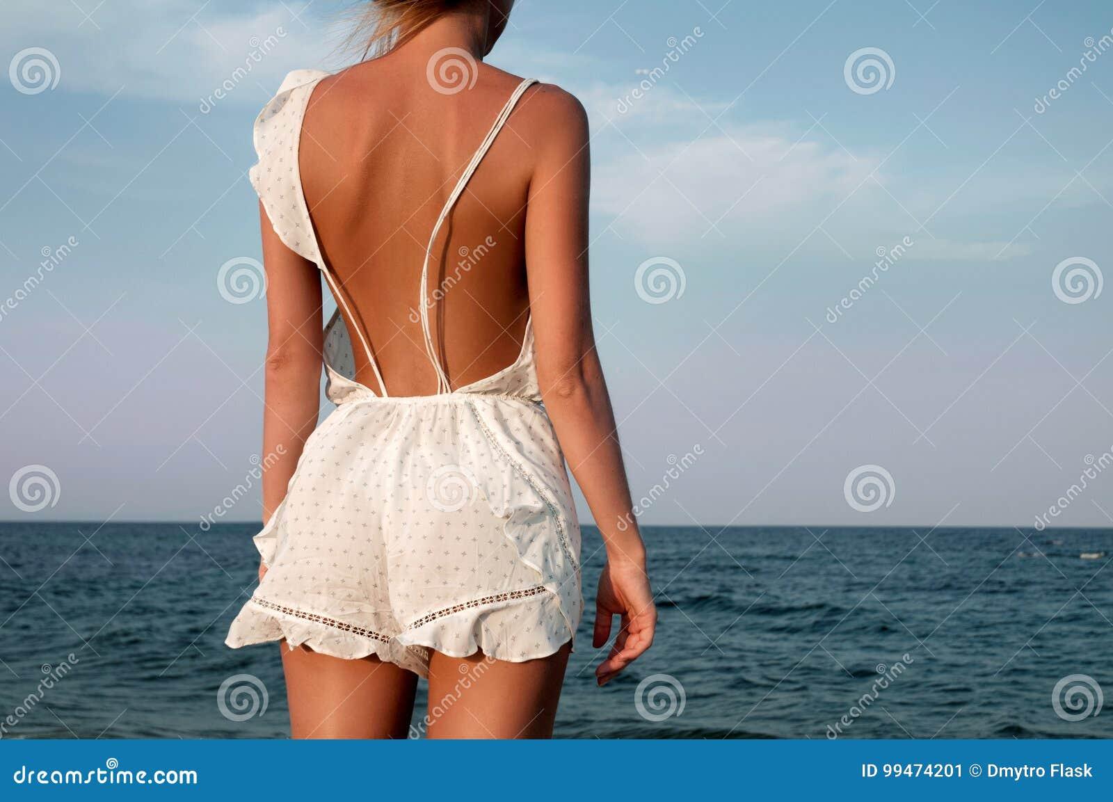 Giovane donna in vestito da estate che sta su una spiaggia e che guarda al mare