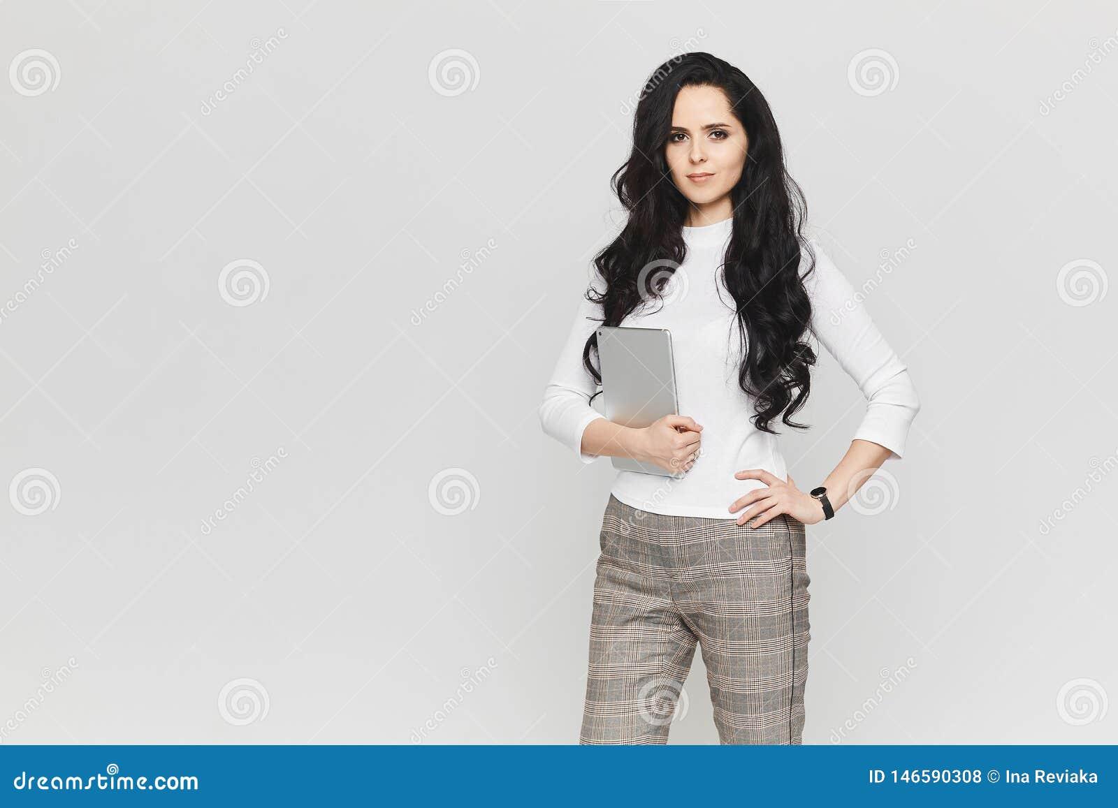 Giovane e bella donna di affari nella blusa bianca e nei pantaloni di plaid alla moda con la compressa in sue mani