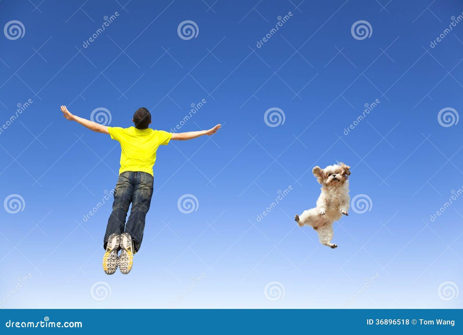 Giovane e cane che saltano nel cielo