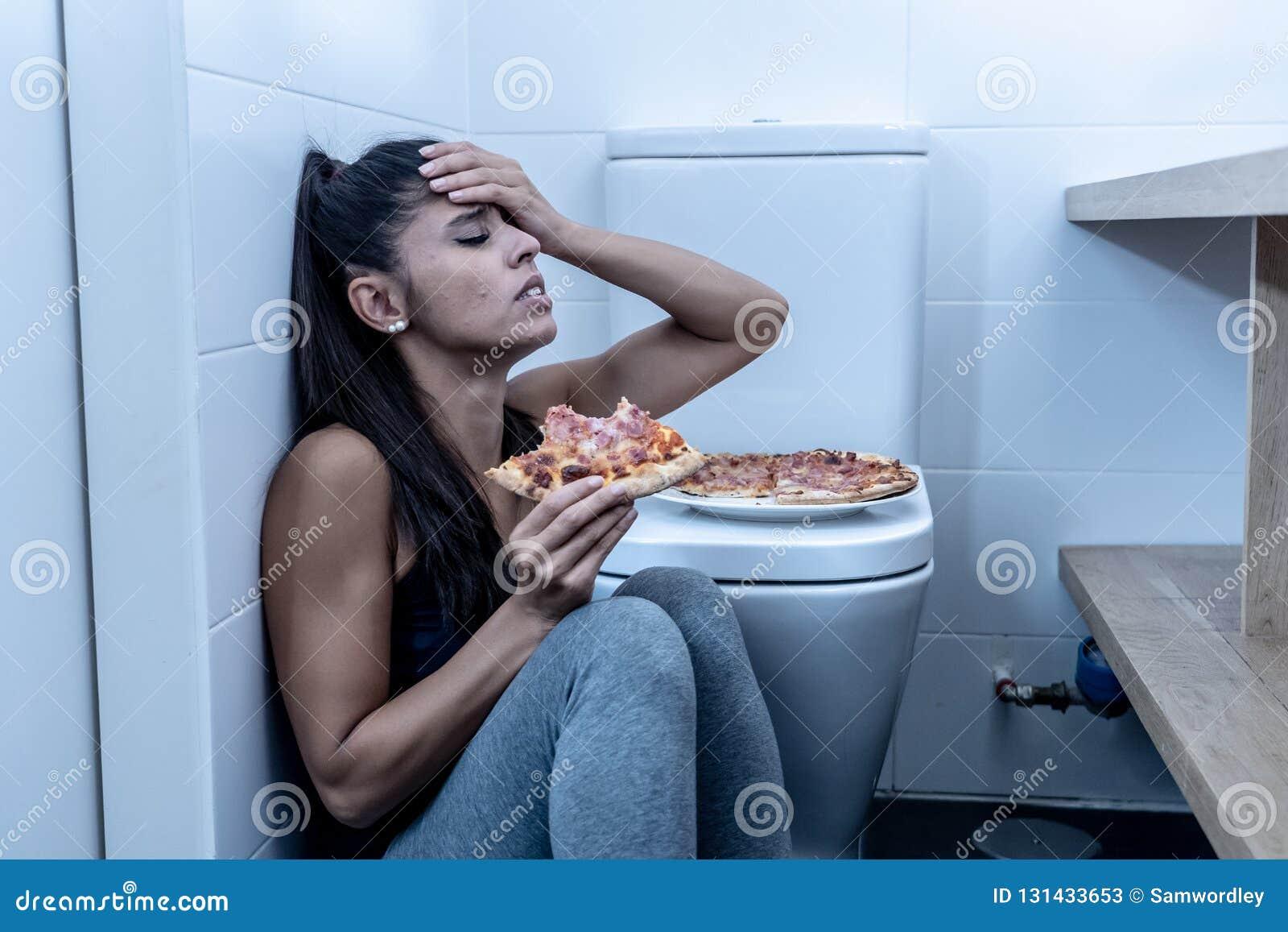 Giovane e giovane donna affetta da bulimia triste attraente che ritiene cibo colpevole e malato mentre sedendosi sul pavimento ac
