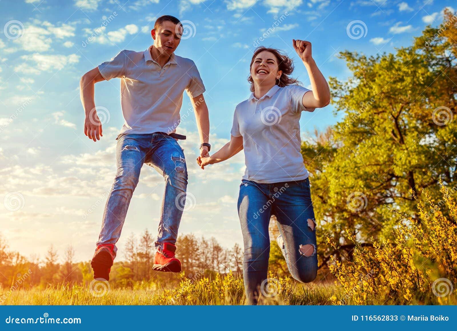 Giovane e funzionamento e salto della donna Coppie divertendosi nel giacimento di primavera al tramonto Risata dei tipi