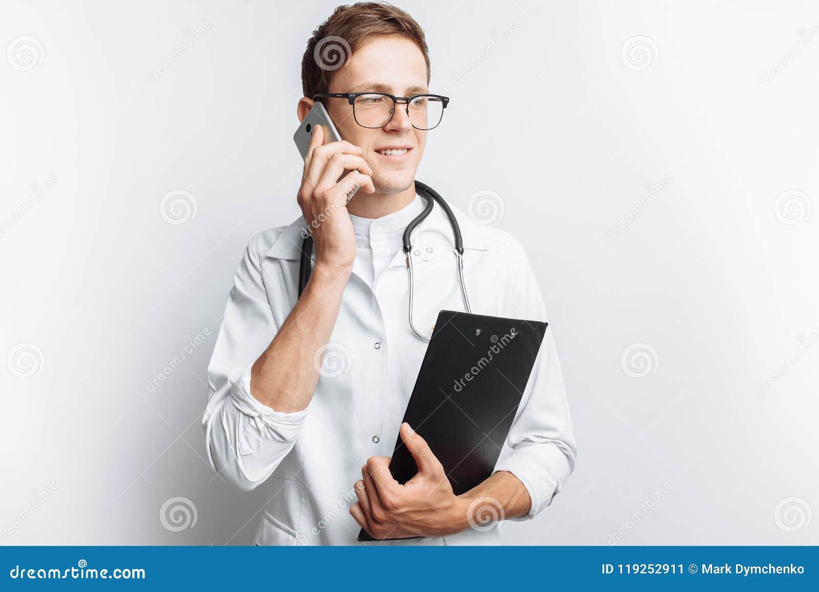 Giovane e medico bello che parla sul telefono con i pazienti, studente dell interno con la cartella a disposizione, fondo bianco,