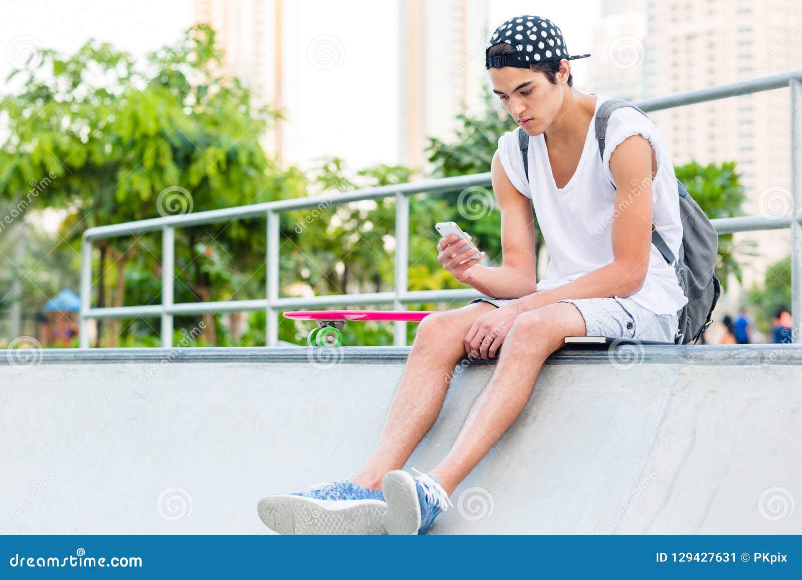 Giovane facendo uso di un cellulare mentre sedendosi allo skatepark