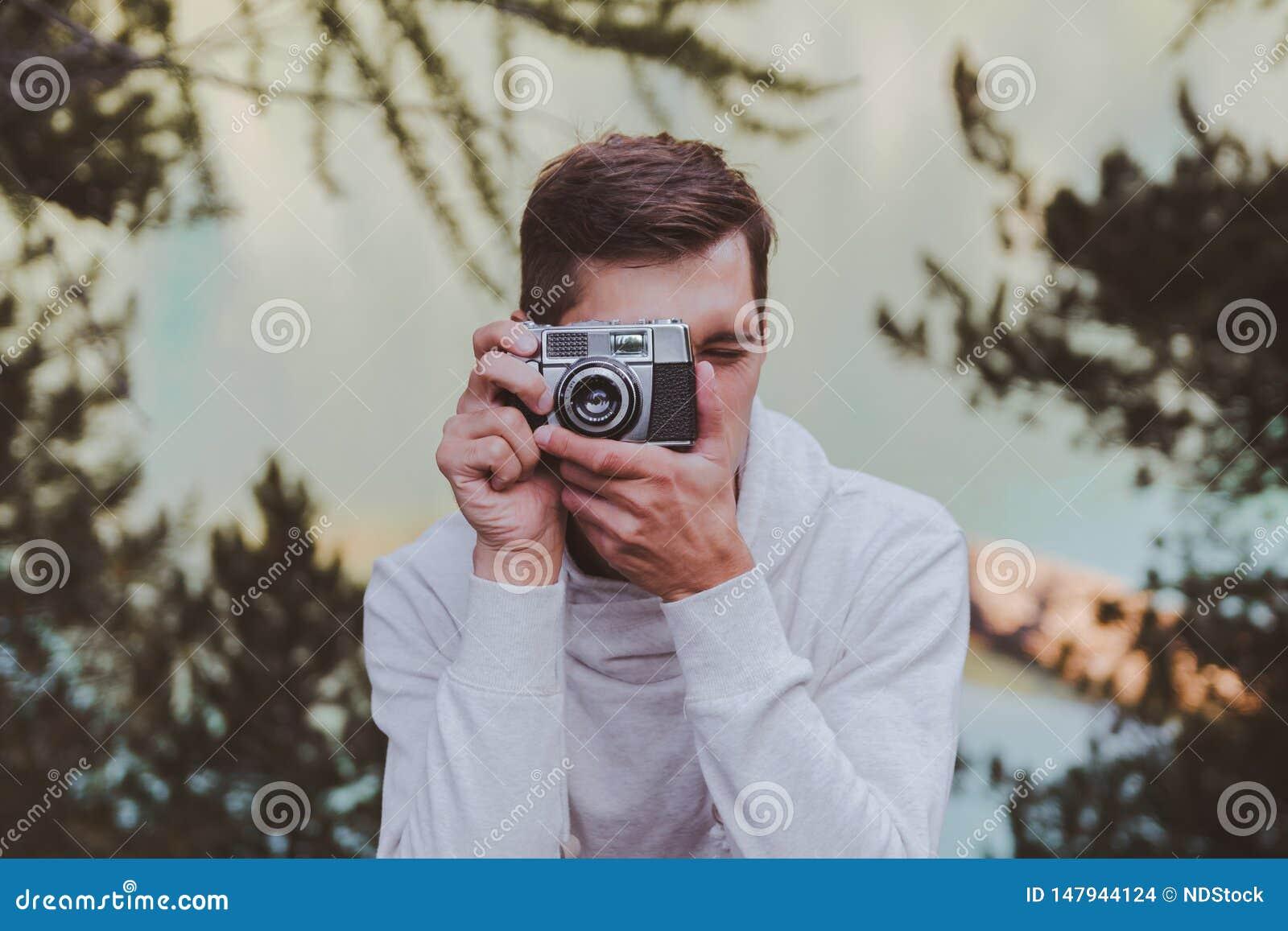 Giovane facendo uso di una macchina fotografica d annata davanti ad un lago del turchese