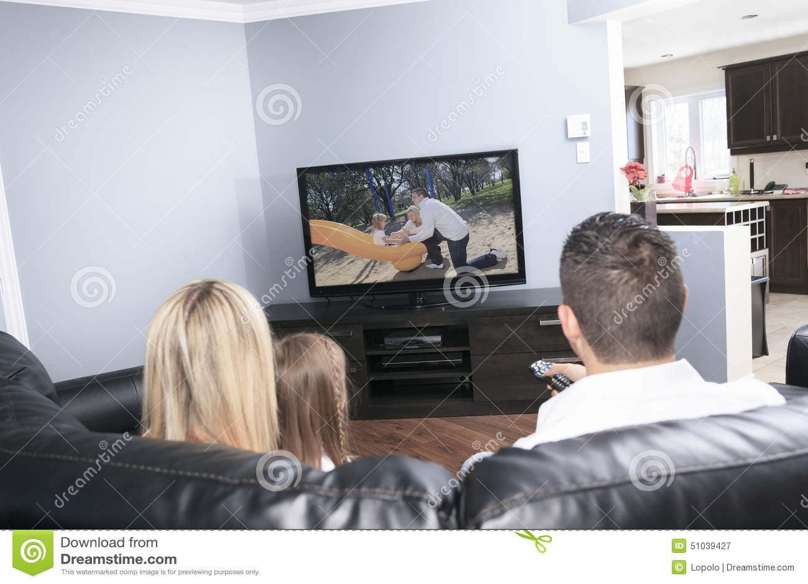 Giovane famiglia che guarda insieme TV a casa