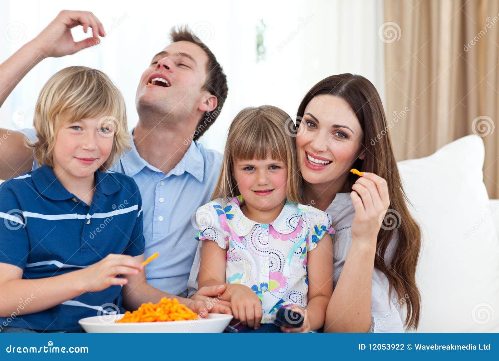 Giovane famiglia che mangia le patatine fritte mentre guardando tv sul