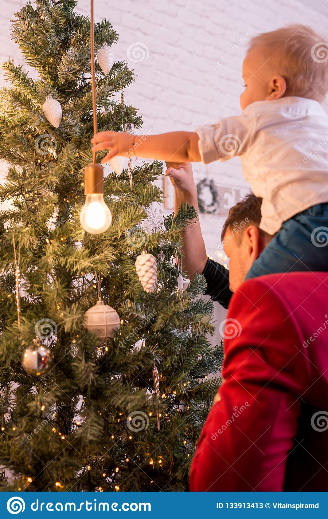 Giovane famiglia felice che si agghinda l albero di Natale Vista posteriore