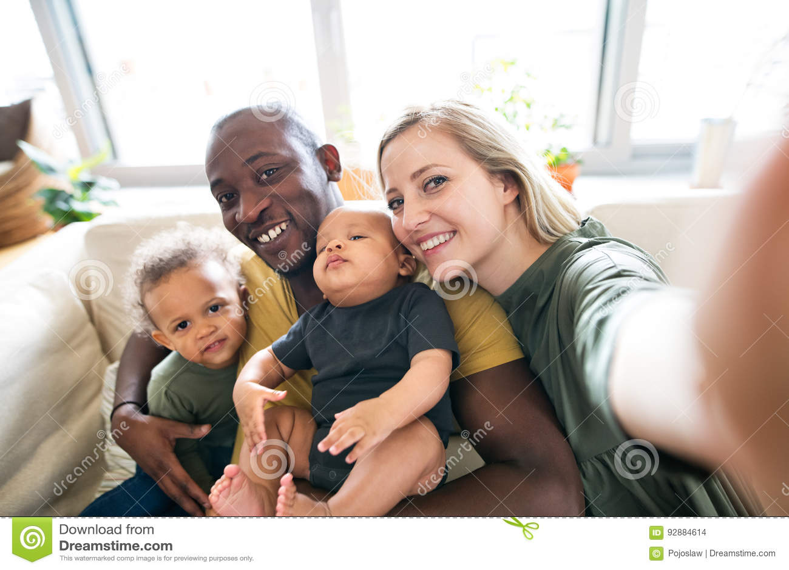 Giovane famiglia interrazziale con i piccoli bambini che prendono selfie