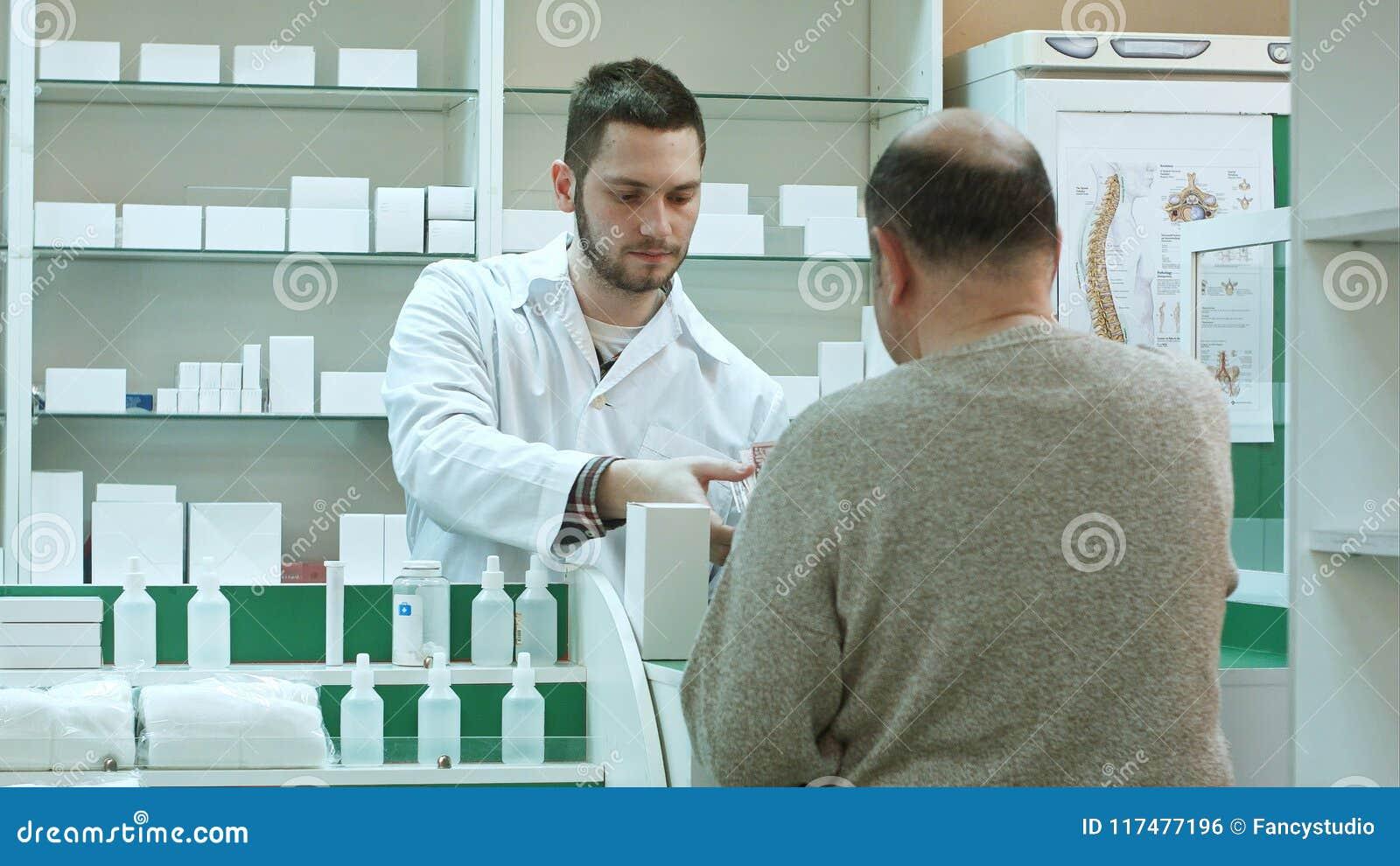 Giovane farmacista che dà droga al cliente dell uomo senior e che prende pagamento nei dollari alla farmacia