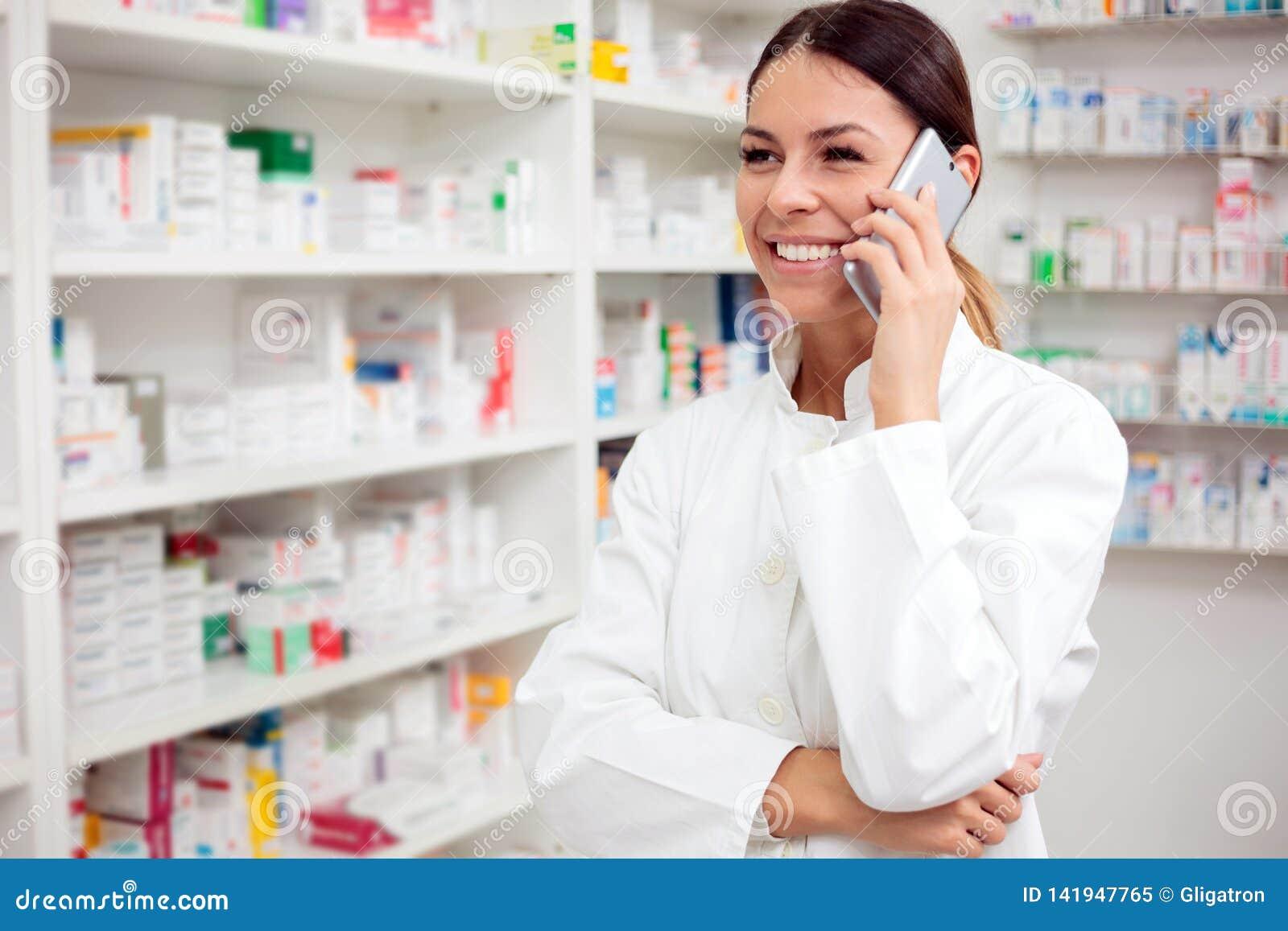 Giovane farmacista femminile sorridente che parla sul telefono