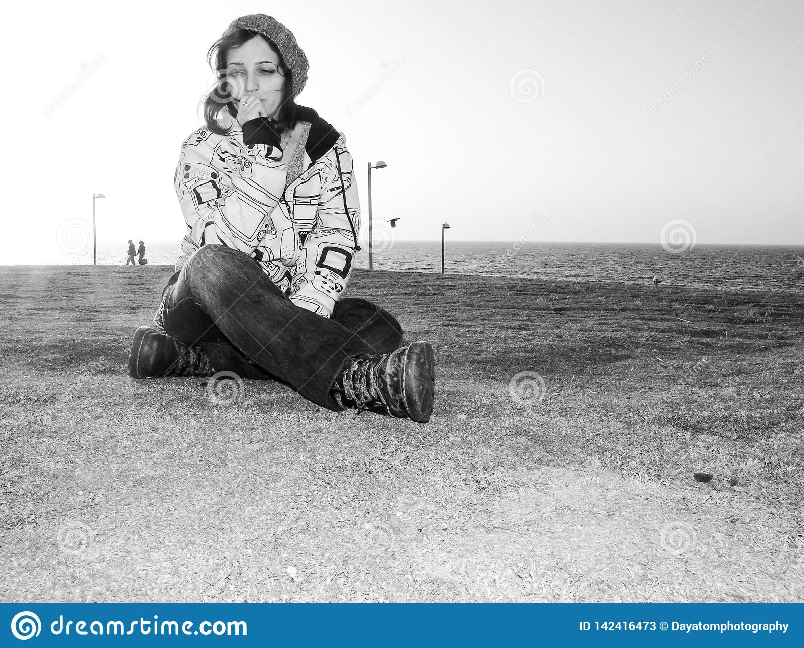 Giovane femmina adulta, abbigliamento casuale d uso, jeans, cappello e una maglia con cappuccio, stile urbano, sedentesi sull erb