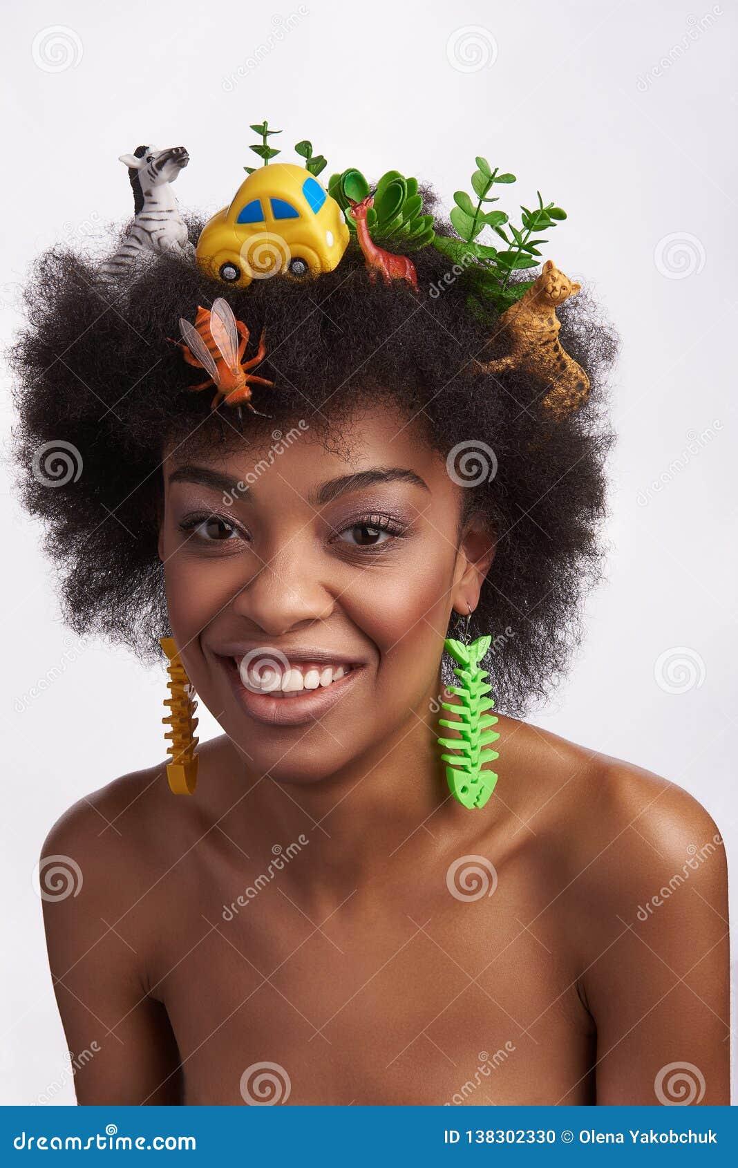 Giovane femmina etnica sorridente nell acconciatura di safari