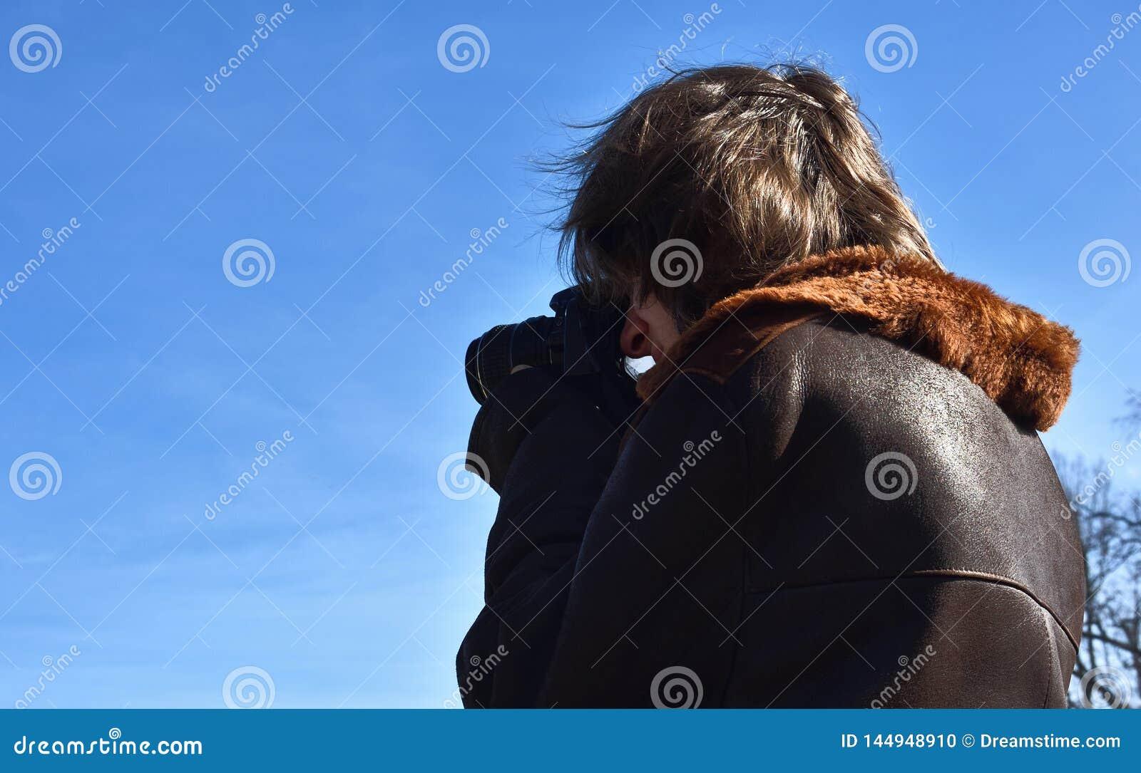 Giovane fucilazione del fotografo di via con la macchina fotografica di DSLR, cielo blu, lampadina, giorno soleggiato
