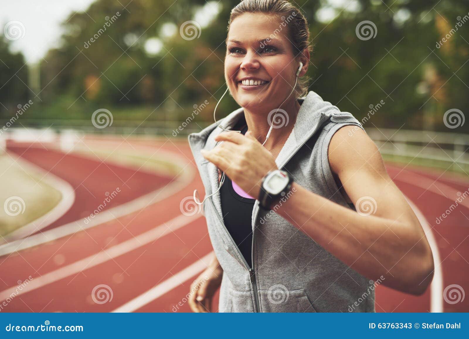 Giovane funzionamento sorridente della donna sullo stadio