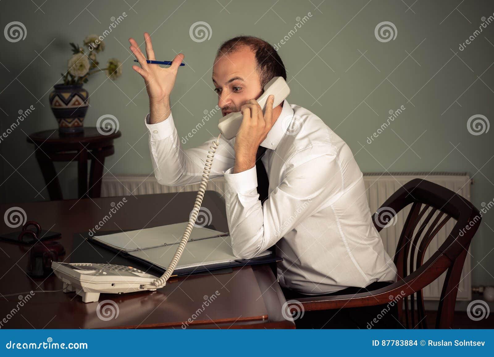 Giovane gesturing dell uomo di affari aggressivo e parlare sul telefono