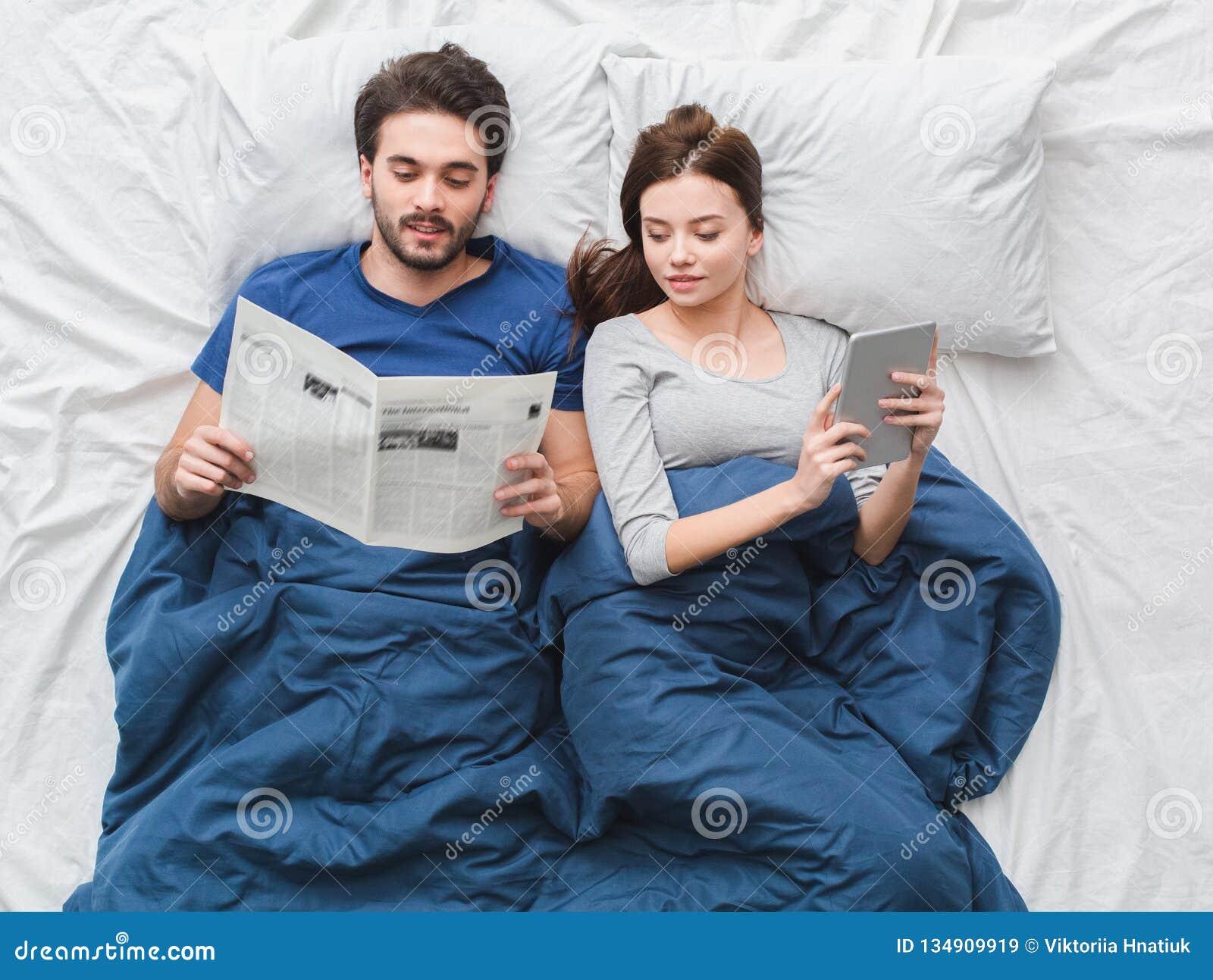 Giovane giornale della lettura del tipo di concetto di mattina di punto di vista superiore delle coppie a letto mentre ragazza fa
