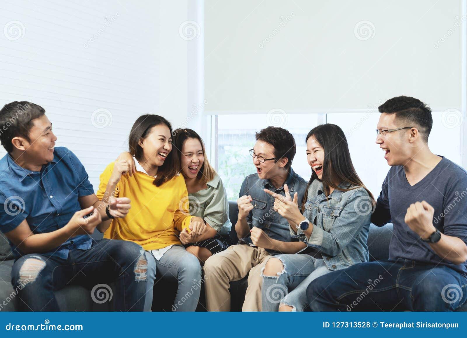 Giovane gruppo asiatico attraente di amici che parlano e che ridono con felice nella riunione della riunione che si siede a casa