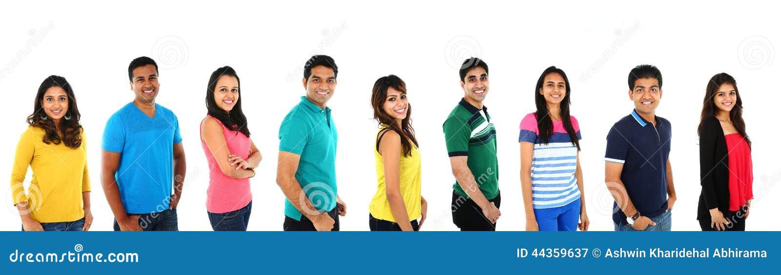 Giovane gruppo di persone indiano/asiatico che esaminano macchina fotografica, sorridente Isolato sulla parte posteriore di bianc