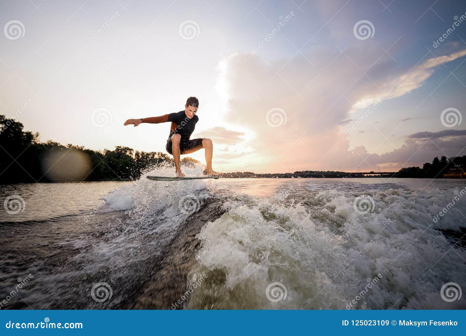 Giovane guida attraente dell uomo sul wakeboard sui precedenti o