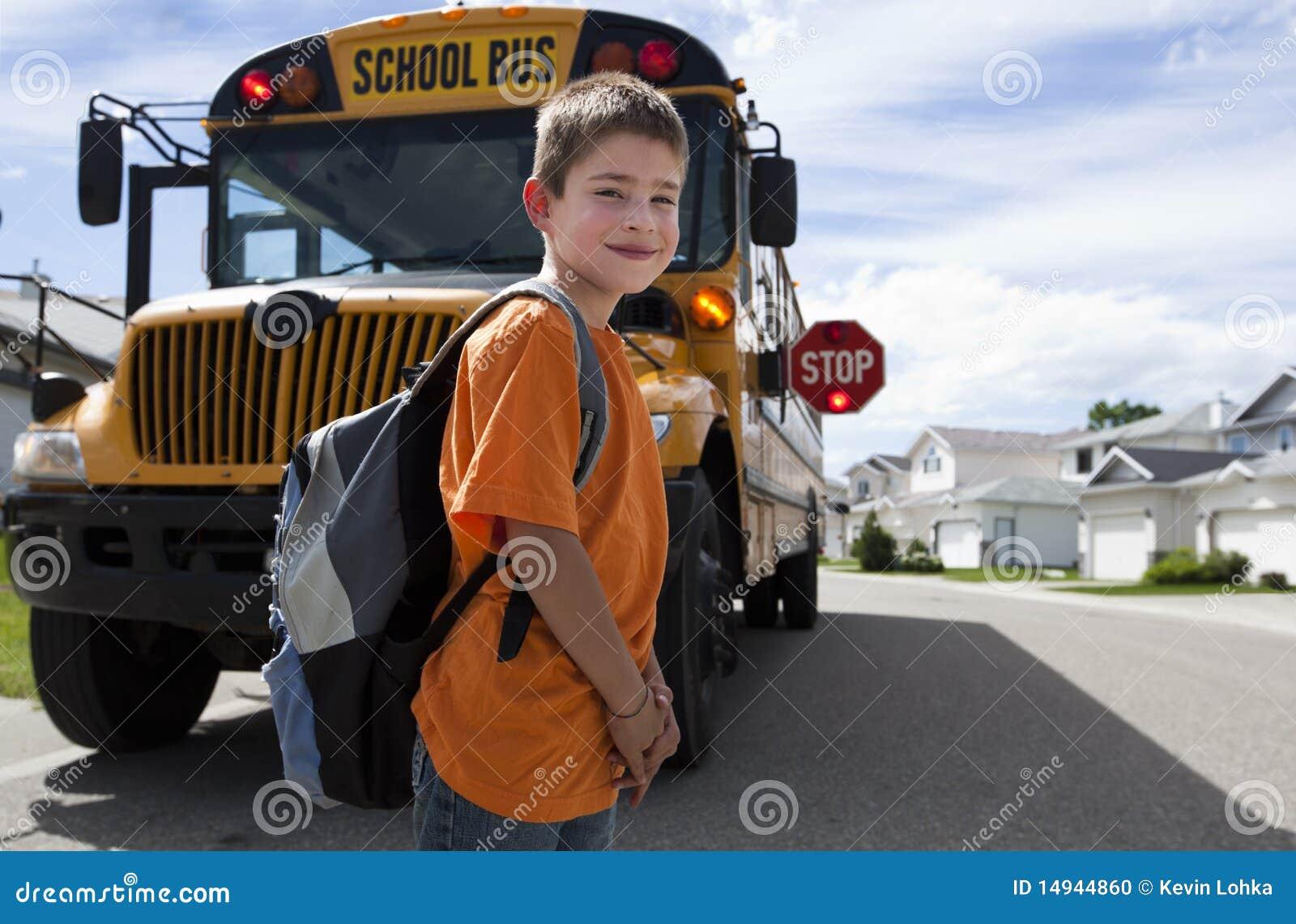 Giovane incrocio del ragazzo davanti allo scuolabus giallo